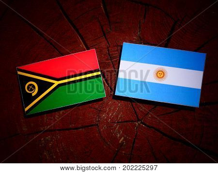 Vanuatu Flag With Argentinian Flag On A Tree Stump Isolated