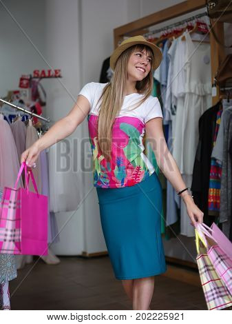 An attractive and happy woman holding colorful shopping bags in her hands among racks with clothes on a mall background. A stylish lady in a beautiful yellow hat in a clothing store. Copy space.