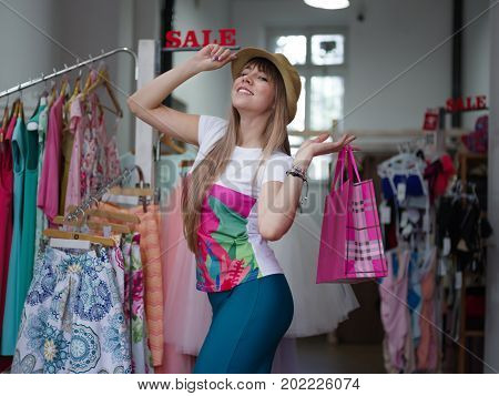 A smiling and happy woman holding colorful shopping bags in her hands among racks with clothes on a mall background. A trendy lady in a beautiful yellow hat in a clothing store. Sale concept.