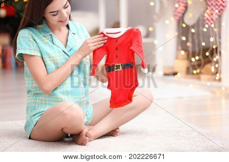 Happy pregnant woman with Santa Claus baby suit sitting on floor at home