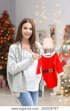 Happy pregnant woman with Santa Claus baby suit in room decorated for Christmas