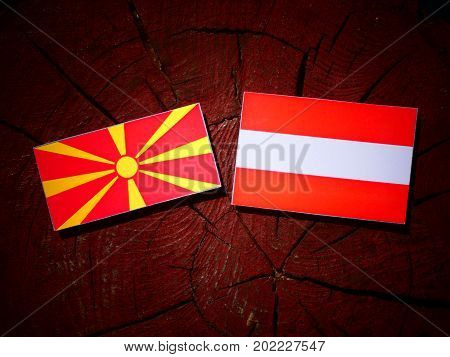 Macedonian Flag With Austrian Flag On A Tree Stump Isolated