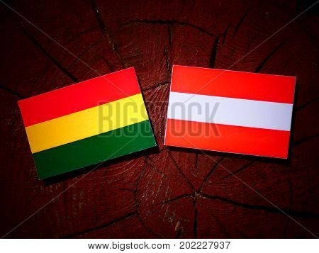 Bolivian Flag With Austrian Flag On A Tree Stump Isolated