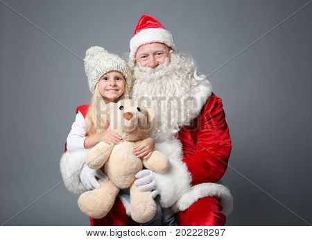 Cute little girl with teddy bear sitting on Santa's lap against color background