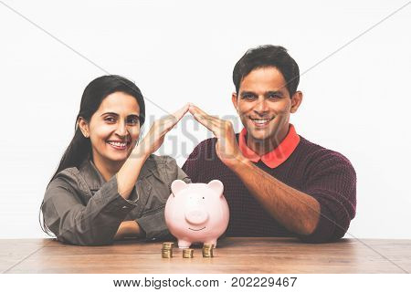 Indian young couple saving money to buy a home or property concept with hands making home shape and pink lay piggy bank or money box
