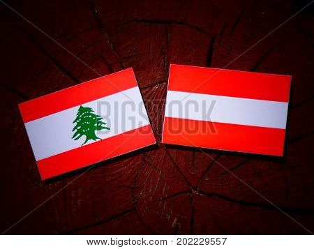 Lebanese Flag With Austrian Flag On A Tree Stump Isolated