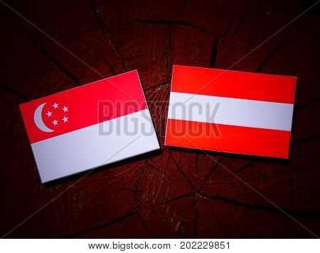 Singaporean Flag With Austrian Flag On A Tree Stump Isolated