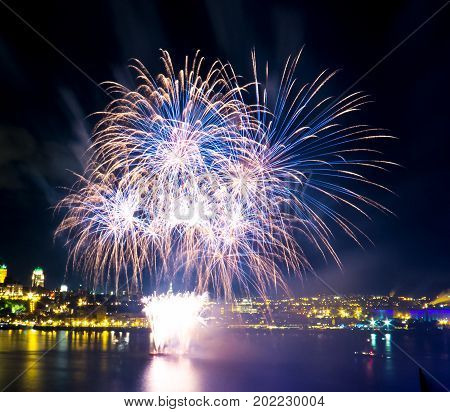 Blue and white fireworks over the Saint-Lawrence River with a part of Quebec city in the background. Quebec, Canada.