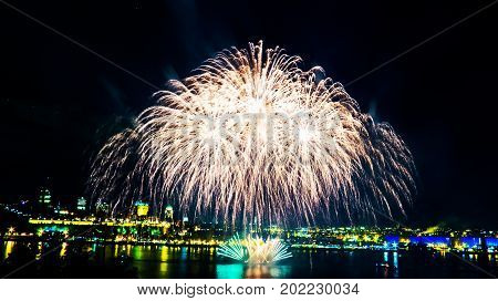 Big white fireworks over the Saint-Lawrence River with a part of Quebec city in the background. Quebec, Canada.