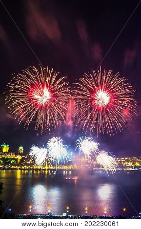Colorful and detailed fireworks over the Saint-Lawrence River with a part of Quebec city in the background. Quebec, Canada.