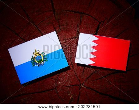 San Marino Flag With Bahraini Flag On A Tree Stump Isolated