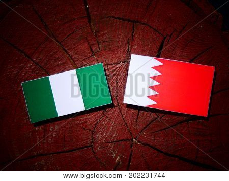Nigerian Flag With Bahraini Flag On A Tree Stump Isolated