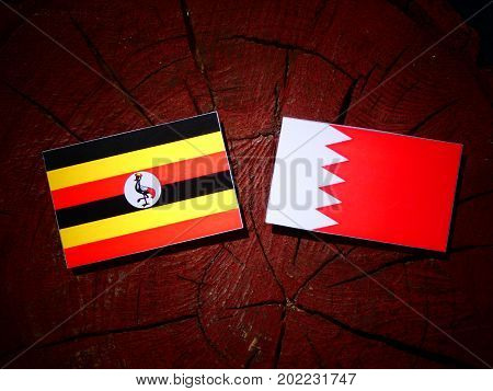 Uganda Flag With Bahraini Flag On A Tree Stump Isolated