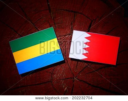 Gabon Flag With Bahraini Flag On A Tree Stump Isolated