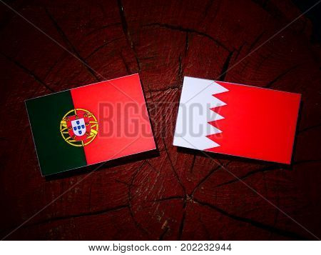 Portuguese Flag With Bahraini Flag On A Tree Stump Isolated