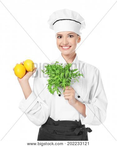 Young female chef with ruccola and lemons on white background