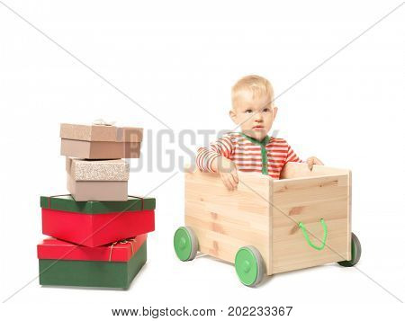 Cute little baby with toy cart and giftboxes on white background. Christmas concept