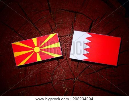 Macedonian Flag With Bahraini Flag On A Tree Stump Isolated