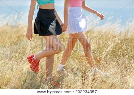 Close-up picture of legs of girls on a natural field background. Two young ladies in colorful clothes walking and resting in the outdoors. Summer holidays and travel concept. Copy space.