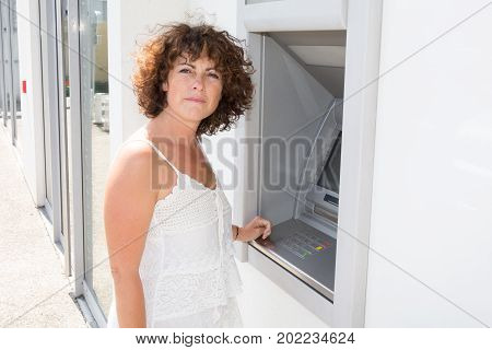 A Caucasian Woman Withdrawing Money From Atm Machine