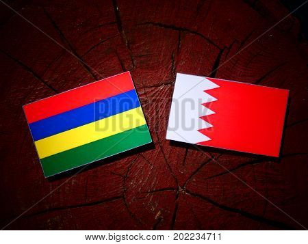 Mauritius Flag With Bahraini Flag On A Tree Stump Isolated