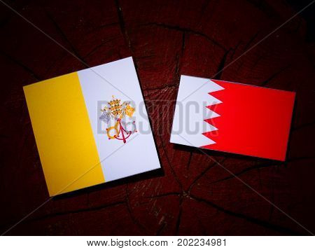 Vatican Flag With Bahraini Flag On A Tree Stump Isolated
