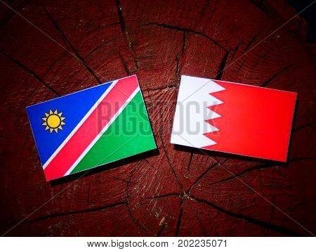 Namibian Flag With Bahraini Flag On A Tree Stump Isolated