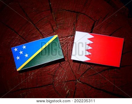 Solomon Islands Flag With Bahraini Flag On A Tree Stump Isolated