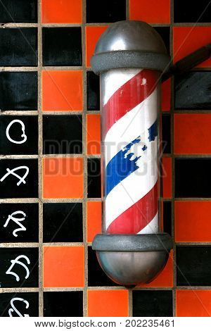 Old barber Shop Revolving pole on an old tiled wall in south Austin, Texas