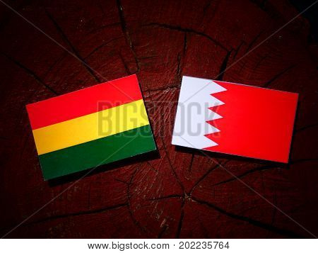 Bolivian Flag With Bahraini Flag On A Tree Stump Isolated