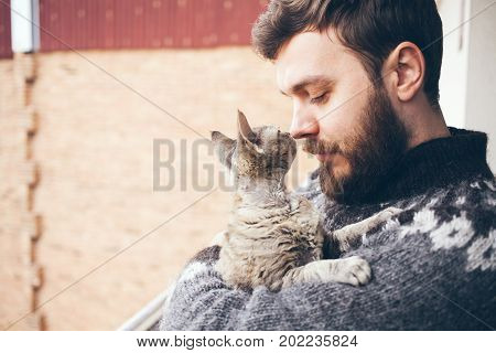 Close-up of a young man who is standing on a balcony with his cat. Home pets. Beard man in icelandic sweater is holding and hugging his cute curious Devon. Copy-space area. Home pets, Lifestyle.