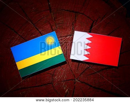 Rwanda Flag With Bahraini Flag On A Tree Stump Isolated