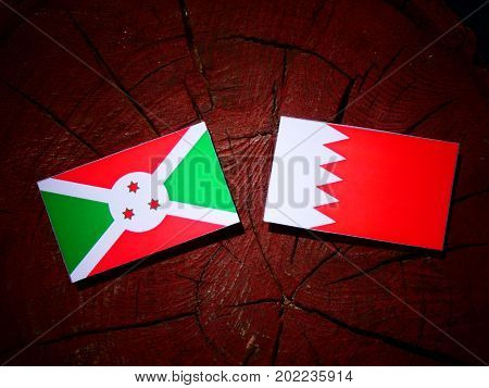 Burundi Flag With Bahraini Flag On A Tree Stump Isolated