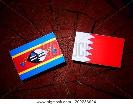 Swaziland Flag With Bahraini Flag On A Tree Stump Isolated
