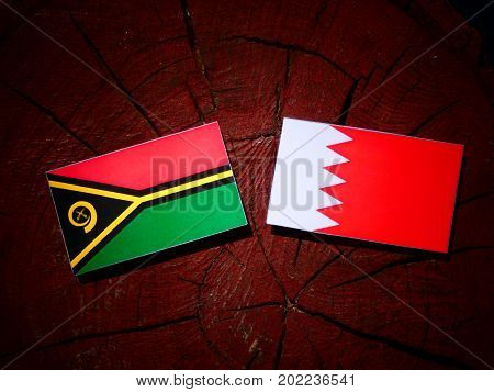 Vanuatu Flag With Bahraini Flag On A Tree Stump Isolated