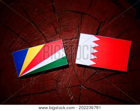 Seychelles Flag With Bahraini Flag On A Tree Stump Isolated