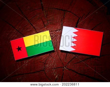 Guinea Bissau Flag With Bahraini Flag On A Tree Stump Isolated