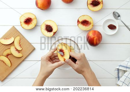 Step By Step Recipe Galette Or Pie With Nectarines. Female Hands Cut Nectarine Into Slices For Pie.