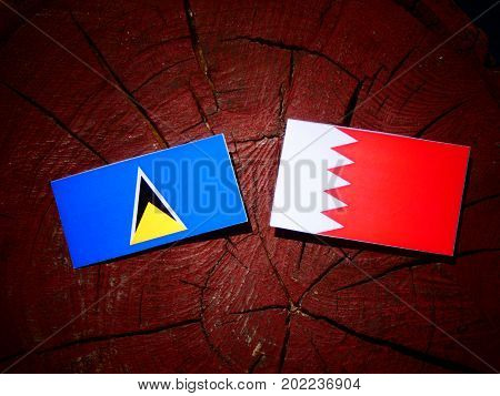 Saint Lucia Flag With Bahraini Flag On A Tree Stump Isolated