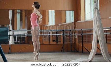 A young girl gracefully performs acrobatics tricks in studios, circus artist - telephoto