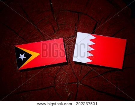 East Timorese Flag With Bahraini Flag On A Tree Stump Isolated