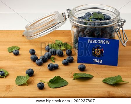 Wisconsin Flag On A Wooden Plank With Blueberries Isolated On White