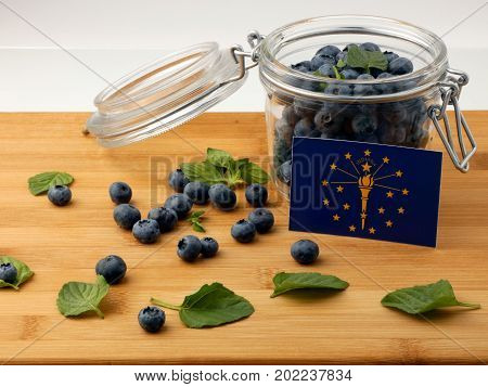 Indiana Flag On A Wooden Plank With Blueberries Isolated On White