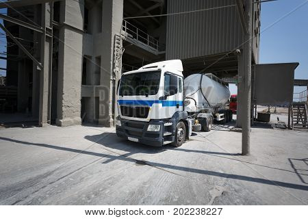A huge, modern, new truck standing in a warehouse outside on a sunny industrial background. White and gray lorry for transporting storage and constructions. Transportation and shipping business.