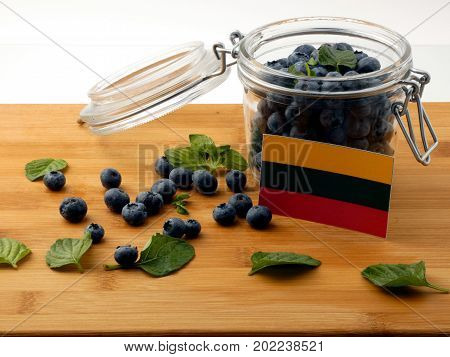 Lithuanian Flag On A Wooden Plank With Blueberries Isolated On White