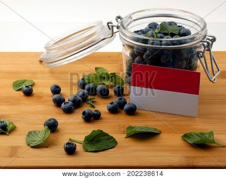 Indonesian Flag On A Wooden Plank With Blueberries Isolated On White