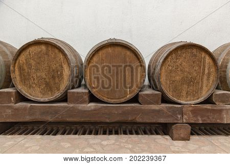 Old oak barrels lie in basement on wooden logsold wine cellars with bottles and barrels