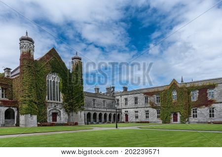 Galway Ireland - August 5 2017: Part of historic Quadrangle on National University of Ireland Campus. Quadrangle building covered in Ivy with two towers under blue sky with white clouds. Green lawn.