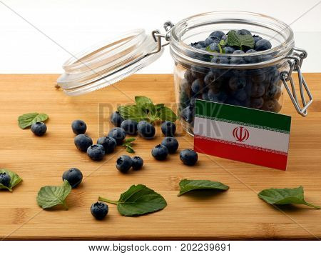 Iranian Flag On A Wooden Plank With Blueberries Isolated On White