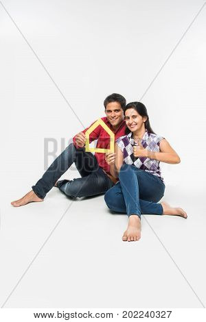 stock photo of Indian or asian smart and cheerful / happy couple holding 3D paper house model and sitting isolated over white background, asian couple and real estate concept.